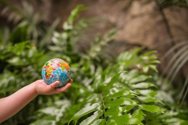 Close-up, de, menino, mão, segurando, globo inflável, bola Foto gratuita