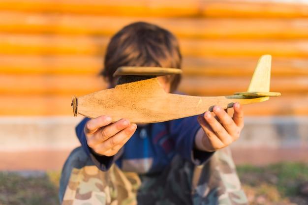 Close-up, de, menino, segurando, avião madeira, em, seu, mãos Foto gratuita