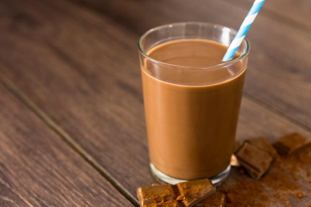 Close-up de milkshake de chocolate com palha e cacau Foto gratuita