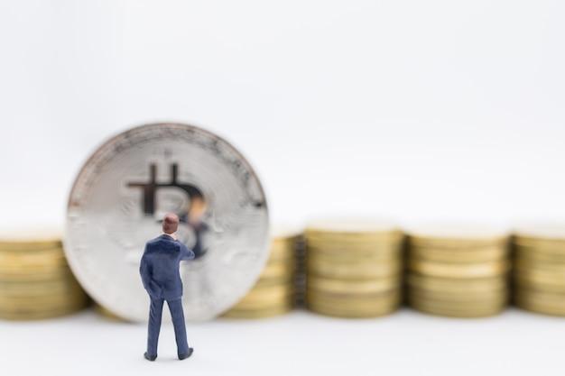 Close-up de miniatura de empresário em pé e olhando para bitcoin e pilha de moedas de ouro Foto Premium