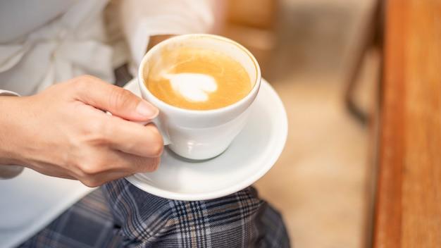 Close up de mulher bonita está bebendo café Foto Premium