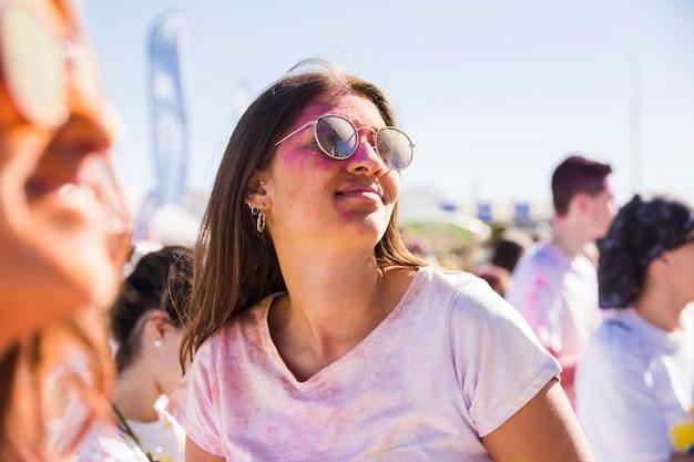 Close-up, de, mulher, desgastar, óculos de sol, tocando, com, holi, cor Foto gratuita