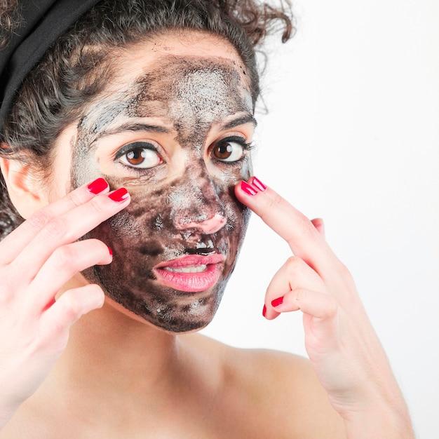 Close-up, de, mulher jovem, aplicando, máscara preta rosto, com, dela, dedos Foto gratuita