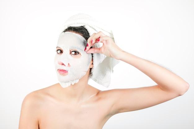 Close-up, de, mulher jovem, puxando, branca, máscara, de, rosto Foto gratuita