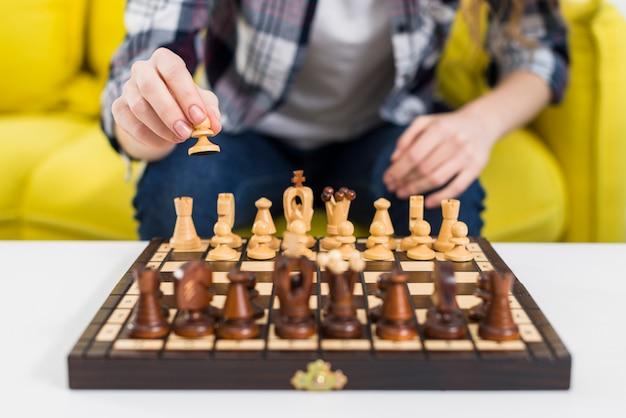 Close-up, de, mulher, mão, jogando xadrez Foto gratuita