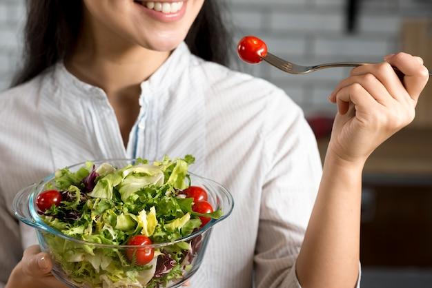 Close-up, de, mulher sorridente, comer, fresco, salada saudável Foto gratuita