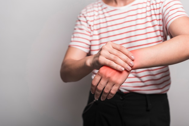 Close-up, de, mulher, tendo, dor, em, pulso, contra, experiência cinza Foto gratuita