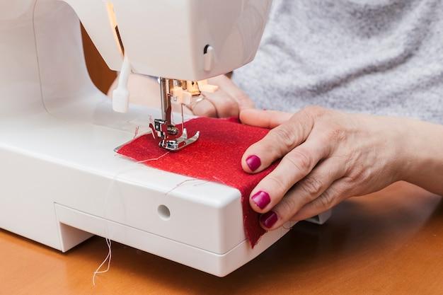 Close-up, de, mulher, trabalhando, ligado, a, máquina de costura Foto gratuita
