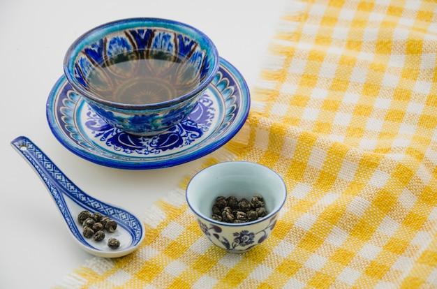 Close-up, de, oolong, xícara chá, com, colher, ligado, toalha de mesa, contra, fundo branco Foto gratuita