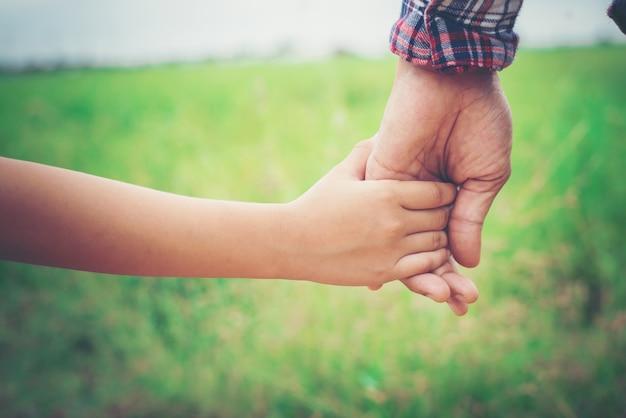 Close up de pai segurando a mão da filha, tão doce, ti família Foto gratuita