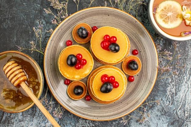 Close up de panquecas de frutas mel com uma colher de pau e uma xícara de chá Foto gratuita