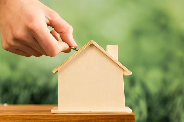 Close-up, de, passe, inserindo, moeda, em, a, casa madeira, ligado, tabela madeira Foto gratuita