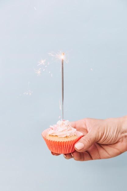 Close-up, de, passe segurar, aniversário, cupcake, com, sparkler, ligado, experiência cinza Foto gratuita