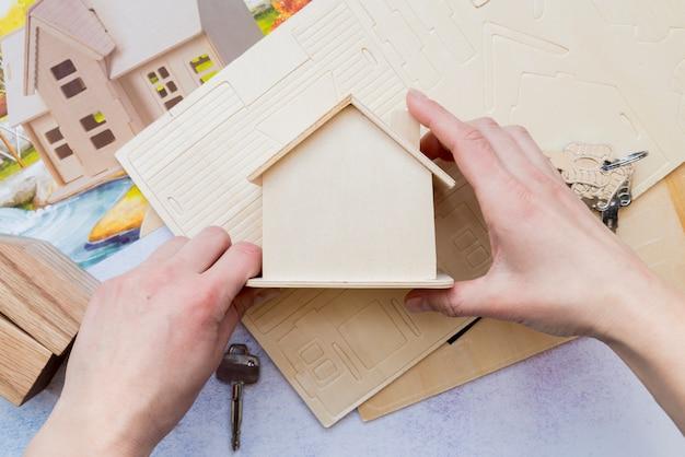Close-up, de, passe segurar, miniatura madeira, casa, modelo Foto gratuita