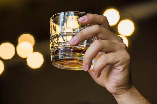 Close-up, de, passe segurar vidro, de, uísque Foto gratuita