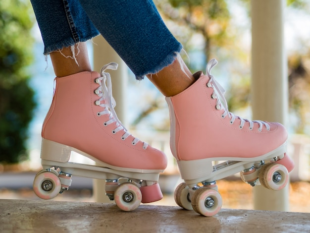 Close-up de patins com mulher em jeans Foto gratuita