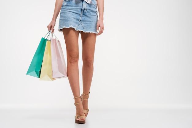 Close-up de pernas femininas em saia segurando sacolas de compras Foto gratuita