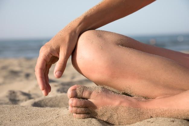 Close-up, de, pés, coberto areia, em, a, praia Foto gratuita