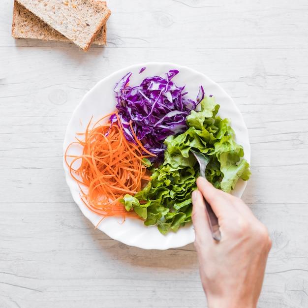 Close-up, de, pessoa, mão, levando, salada vegetal, com, colher, ligado, escrivaninha madeira Foto gratuita