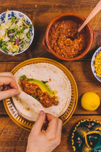 Close-up, de, pessoas, mão, preparar, envoltório, carne, tacos Foto gratuita