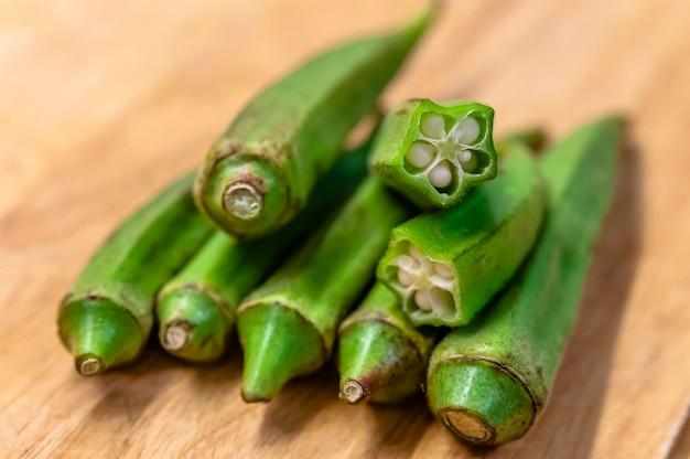 Close-up de pilha de quiabo orgânico em madeira. okra frutas na tábua de cortar Foto Premium