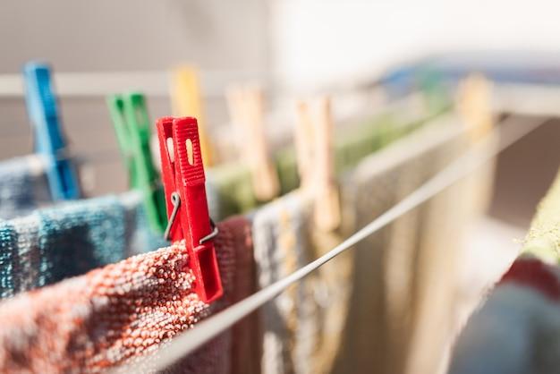 Close-up de pinos coloridos e pendurar roupas ou toalhas de cozinha. prendedores de roupa plásticos coloridos em um varal. pino vermelho. tarefas domésticas. dever de casa. lavanderia. lave as roupas. copie o espaço. Foto Premium