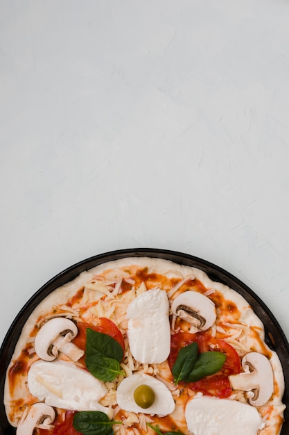Close-up de pizza caseira italiana em fundo cinza Foto gratuita