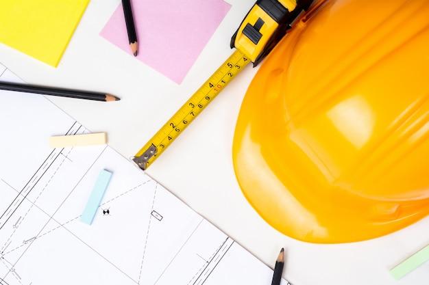 Close-up de plantas, fita métrica e capacete de construção amarela. conceito de engenheiro Foto gratuita