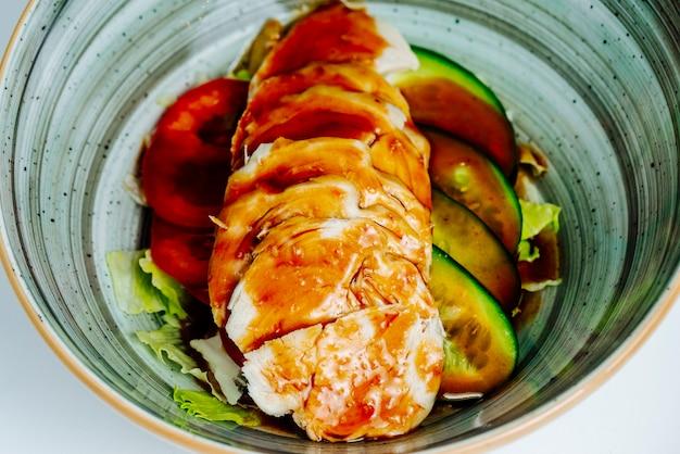 Close-up de prato de frango com pepino, alface, pimentão e molho de soja Foto gratuita