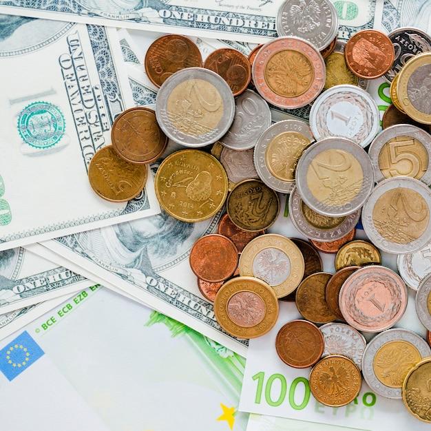 Close-up de propagação de moedas e nos notas de cem dólares Foto gratuita