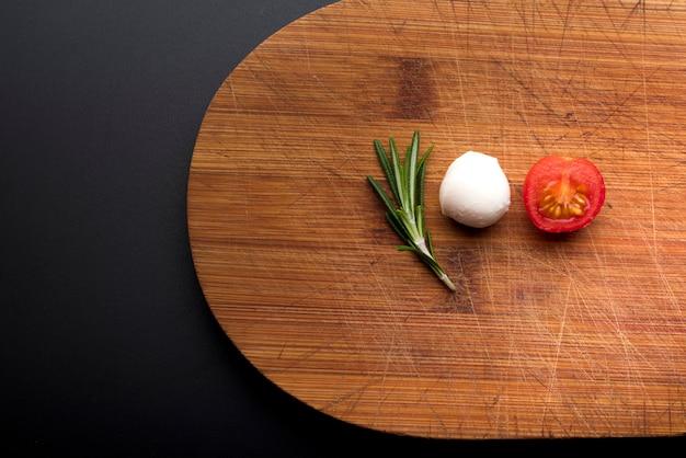 Close-up de queijo fresco; alecrim e meio tomate na tábua de cortar Foto gratuita