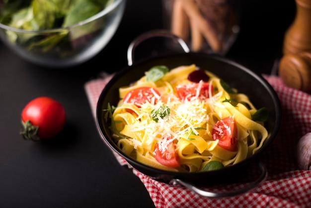 Close-up, de, queijo, saudável, tagliatelle, macarronada, em, recipiente, com, fatias, de, tomate cereja Foto gratuita