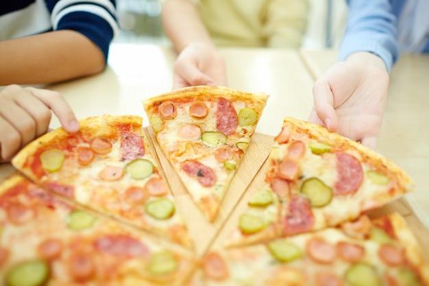 Close-up de rapazes agarrando pizza quente Foto gratuita