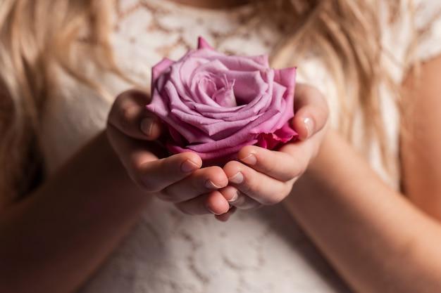 Close-up de rosa nas mãos da mulher Foto gratuita