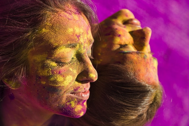Close-up, de, rosto feminino, coberto, com, multicoloured, holi, cor Foto gratuita