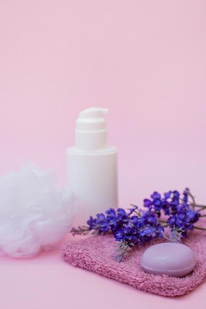 Close-up de sabão; toalha; flor de lavanda; loofah e frasco cosmético na superfície rosa Foto gratuita