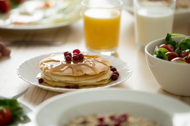 Close-up de saborosas panquecas servidas com calda e frutas Foto gratuita