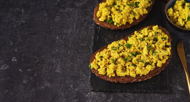 Close-up de sanduíches de salada de ovo vegan colorido sobre fundo preto Foto Premium