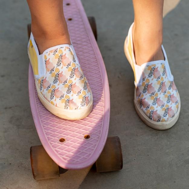 Close-up, de, sapatos modelados, e, cor-de-rosa, skateboard Foto gratuita