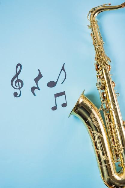 Close-up, de, saxofones, com, notas musicais, ligado, experiência azul Foto gratuita