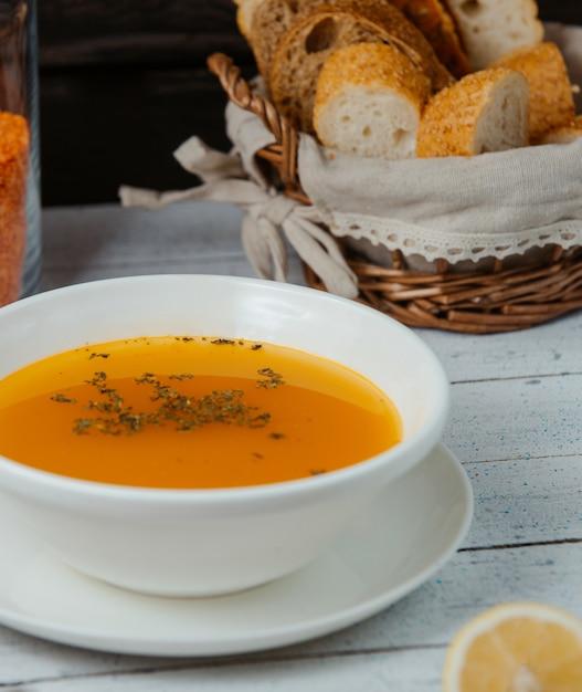 Close-up de sopa de lentilha em tigela servida com pão Foto gratuita