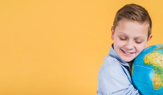 Close-up, de, sorrindo, menino, abraçar, globo, contra, fundo amarelo Foto gratuita
