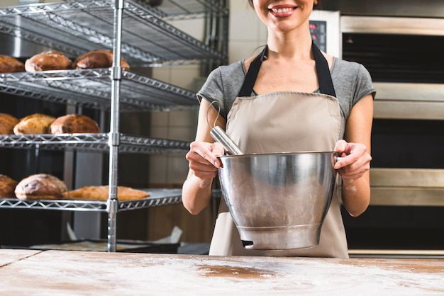 Close-up, de, sorrindo, mulher jovem, segurando, misture tigela, em, panificadora Foto gratuita