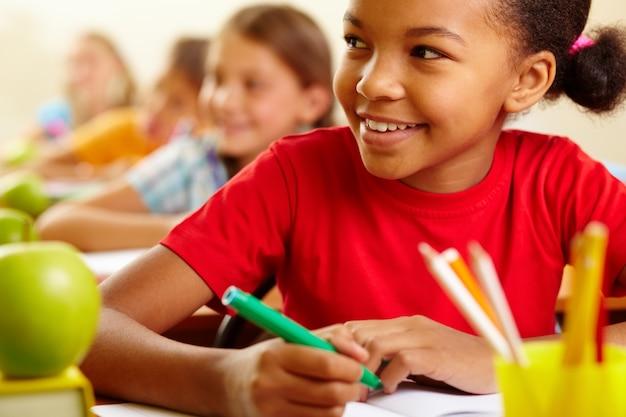 Close-up de sorriso do estudante com os colegas de fundo Foto gratuita