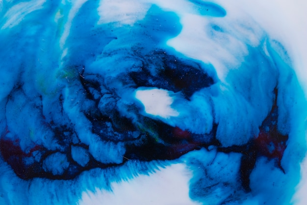 Close-up de tinta azul dissolve-se em tinta líquida branca Foto gratuita