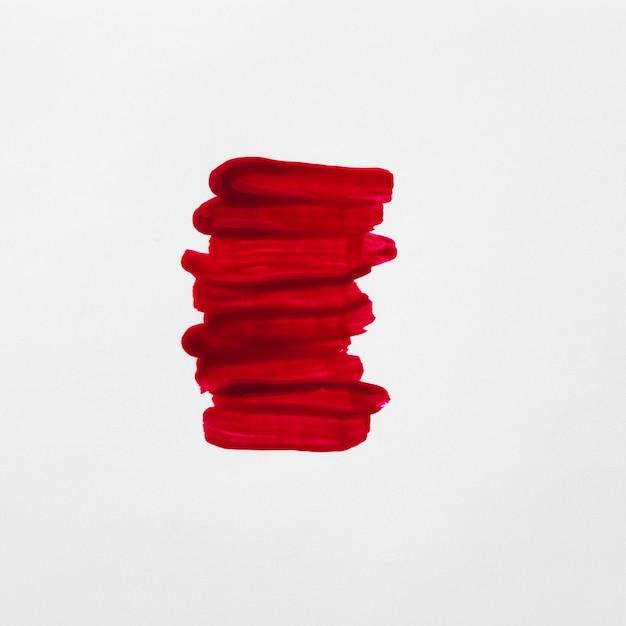 Close-up de traços de verniz vermelho sobre fundo branco Foto gratuita