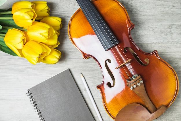 Close-up de tulipas; diário; lápis e violino no fundo de madeira Foto gratuita