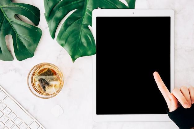 Close-up, de, um, apontar pessoa, dedo, sobre, a, tablete digital, com, vidro chá, ligado, marmore, textured, fundo Foto gratuita