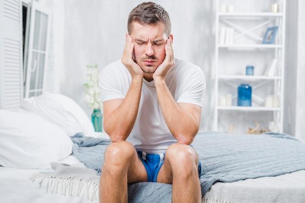 Close-up, de, um, assento homem, cama, tendo, dor de cabeça Foto gratuita