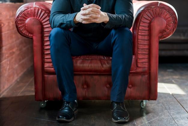 Close-up, de, um, assento homem, ligado, poltrona, com, seu, mão clasped Foto gratuita